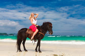 Happy girl walking with horse on a tropical beach — Stock Photo
