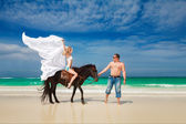 Young couple in love walking with the horse on a tropical beach. — Foto de Stock