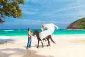 Jong paar in liefde lopen met het paard op een tropisch strand. — Stockfoto