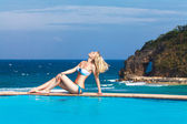 Young beautiful blonde girl is next to the pool. Tropical sea in — Stock Photo