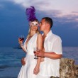 Bride and groom on a tropical beach drinking wine from glasses w — Stock Photo #51590413