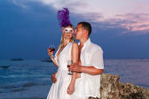 Bride and groom on a tropical beach drinking wine from glasses w — Stock Photo
