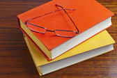 Old dusty books and glasses on the wooden table — Stock Photo