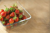 Strawberry fruit in a glass container on a wooden surface. Bokeh — Stock Photo
