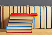 Pile of books on a wooden surface against the background of a nu — Stock Photo