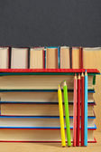 Pile of books and colored pencils on a wooden surface against th — Stock Photo