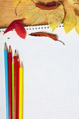Notebook with colored pencils and autumn leaves on a wooden surf — Stock Photo