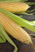 A corn cob on a wooden table — Stock Photo