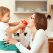 Happy mother with a baby in the kitchen — Stock Photo