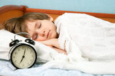 The boy in bed with wake-up clock — Stock Photo