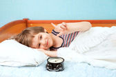 Small boy in bed with alarm clock — Foto Stock