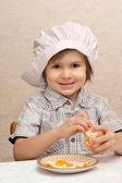 Little boy peels orange — Stock Photo
