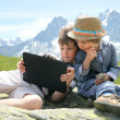 Children sit on stone in mountains — Stock Photo