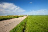 """The road with sign """"dangerous corner"""" and wind turbines — Stock Photo"""