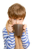 The boy in scarf drinks tea — Stock Photo
