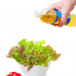 Hands pour oil in salad — Photo