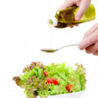 Hands pour olive oil in salad — 图库照片