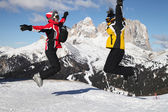 Skiers jumping against big mountain — Stock Photo