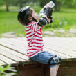 Boy on roller skates drinks water — Stock Photo #50289007
