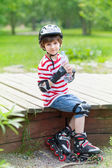 Ittle boy on rollers with a bottle — Stock Photo