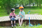 Children with rollers and scooter — Stock Photo