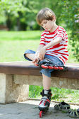Kid put on roller skates on a bench — Stock Photo