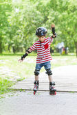 Boy on rollers in the summer park — Stock Photo