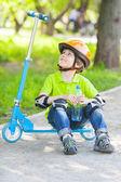 Boy sits on kick scooter — Stock Photo