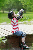 Boy on roller skates drinks water — Stock Photo