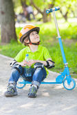 Young boy with  bottle   on kick scooter — Stock Photo