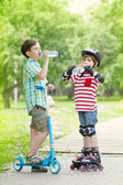 Children with scooter and rollers drink water — Stock Photo