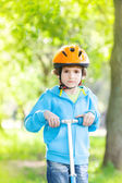 Young boy riding kick scooter in park — Stock Photo