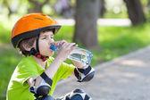 Boy  drinks water from  bottle — Stock Photo