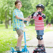 Two boys with scooter and rollers — Stock Photo #50459785