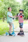 Two boys with scooter and rollers — Стоковое фото