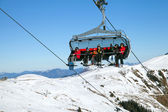 Chair lift with skiers — Stock Photo