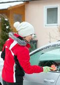 Woman scrapes car window — Stock Photo