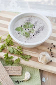 Mushroom cream soup served with garlic and greens — Stock Photo