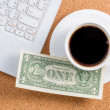 Dollar on a cup of coffee and laptop place — Stock Photo