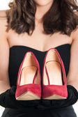 Woman Holding A Pair Of Red Shoes — Stock Photo