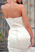 Close up of bride back with white dress and earrings — Stock Photo