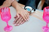 Bride and groom holding hands on table — Stock Photo