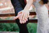 Bride and groom holding wedding ring in hand — Stock Photo