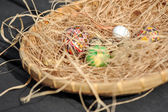 Easter painted eggs and hay basket — Stock Photo
