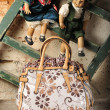 Fashion handbag on natural old wall background and cute dolls — Stock Photo