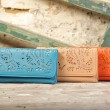 Colorful wallets on natural old wall background — Stock Photo #42395515