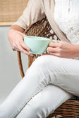 Woman sitting on chair with tea mug in hand — Stock Photo