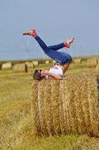 Mladá žena uvolňující na balíku sena — Stock fotografie
