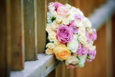 Beautiful floral bouquet and wooden fence — Stock Photo