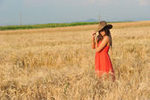 Beautiful woman with orange dress and hat standing in wheat field — Стоковое фото